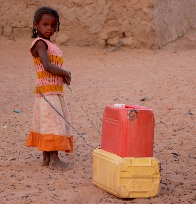 A child hauls jerry cans with water